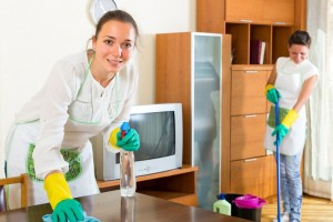 Female cleaners cleaning room .